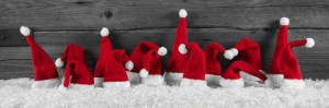 Humorously red, grey and white wooden christmas background with santa hats.